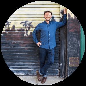 David Currie - Brisbane Financial Advisor at Wealthy Self leaning against a street art wall